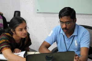 A man and a woman working together at a laptop computer