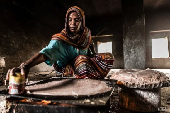 A Sudanese woman demonstrates how to make kisra, a traditional bread or porridge in Sudan and South Sudan. Photo by Mohamed Elfatih Hamadien, freely licensed under CC BY-SA 4.0.