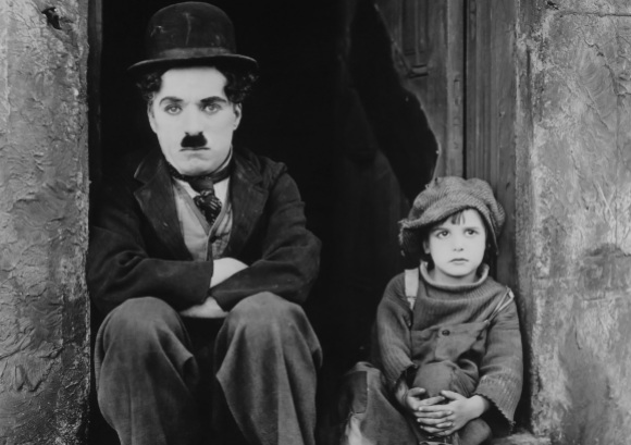 Promotional photo for Chaplin's The Kid. Chaplin is sitting on a concrete step with a young child to his left.