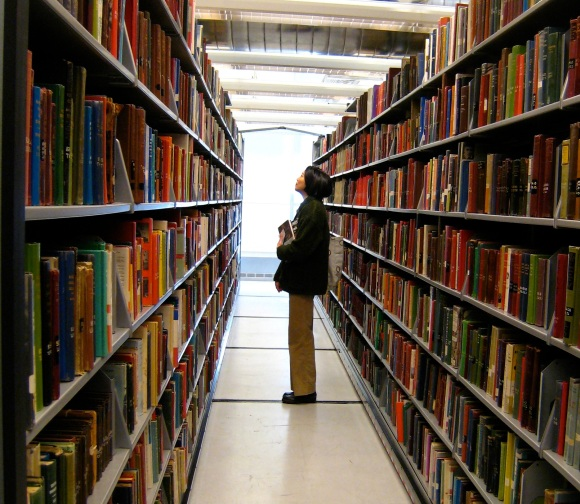 A person peruses bookstacks at the Minneapolis Public Library.