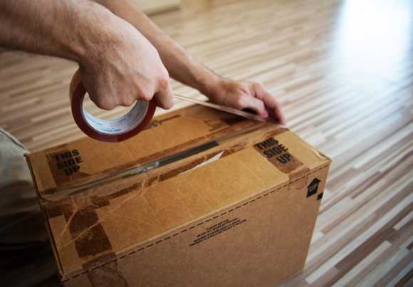 A person tapes up a filled moving box.