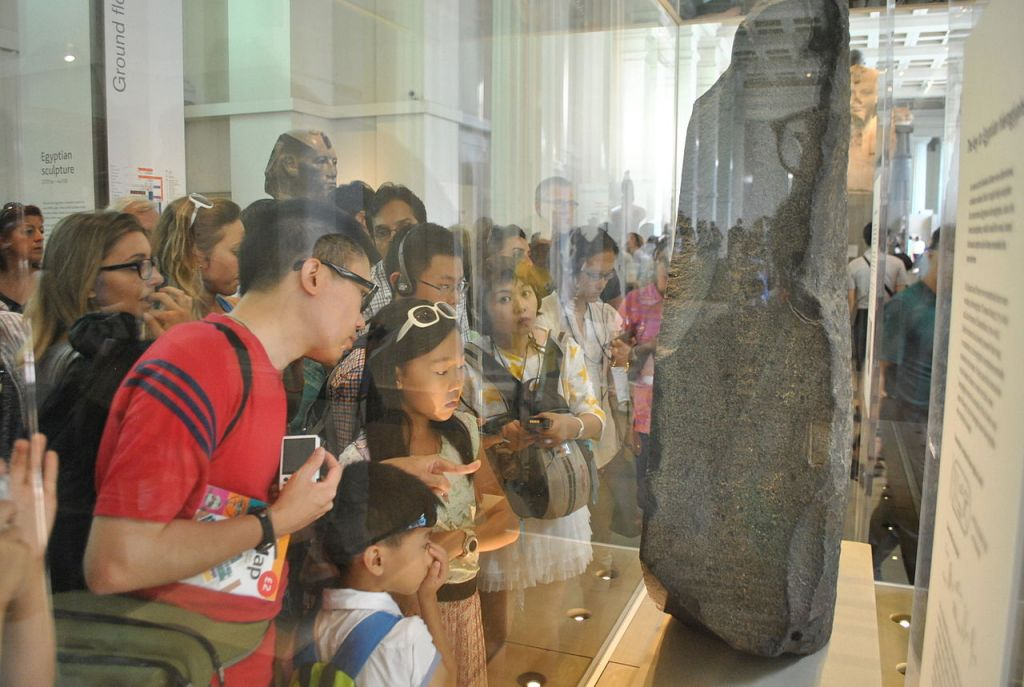 Tourists looking at Rosetta Stone at British Museum.