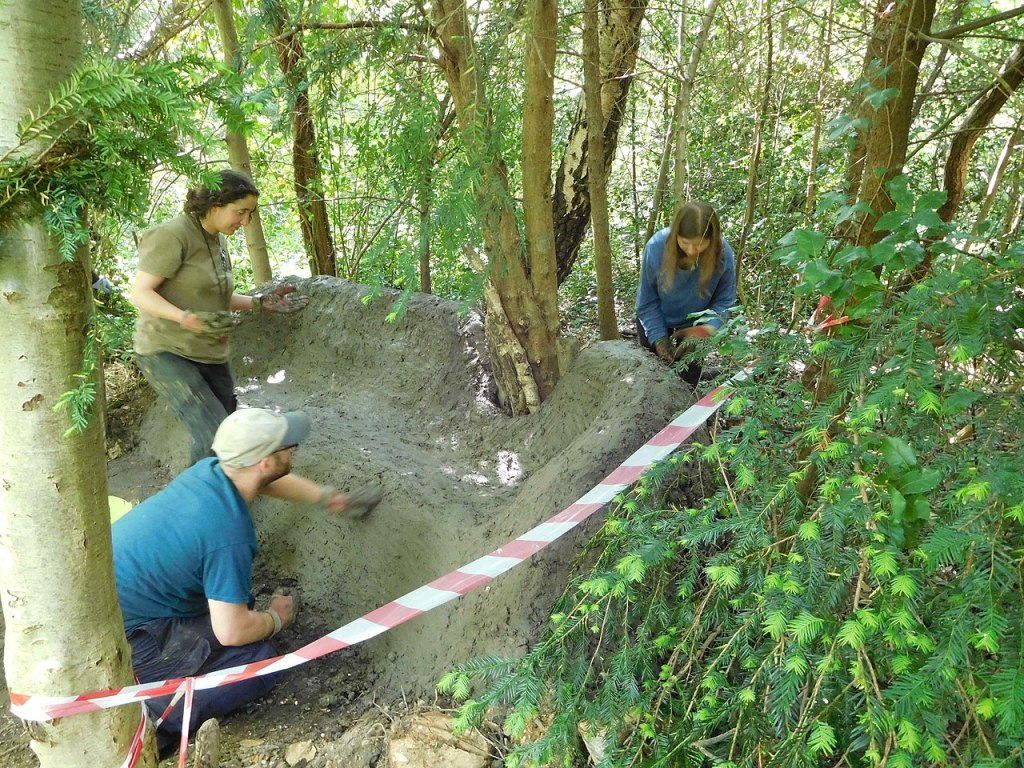 Staff and volunteers smoothing surface of mud sofa in Gunnersbury Triangle local nature reserve